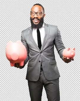 Biznesowy czarnego mężczyzna oszczędzanie z prosiątko bankiem