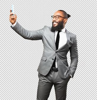 Biznesowy czarny człowiek bierze selfie