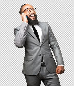 Biznesowy czarny człowiek opowiada na telefonie komórkowym