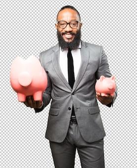 Biznesowy czarny mężczyzna oszczędzanie z prosiątko bankiem