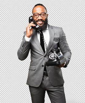 Biznesowy murzyn trzyma telefon