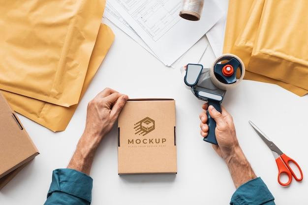Bliska ręce przygotowujące pudełko do dostawy