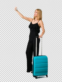 Blond dziewczyna podróżuje z jej walizką bierze selfie z wiszącą ozdobą