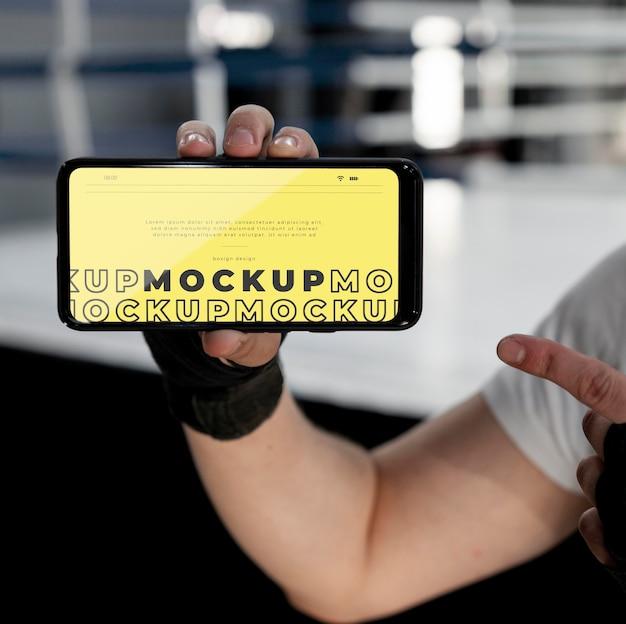 Boks sportowiec trzymający makietę telefonu