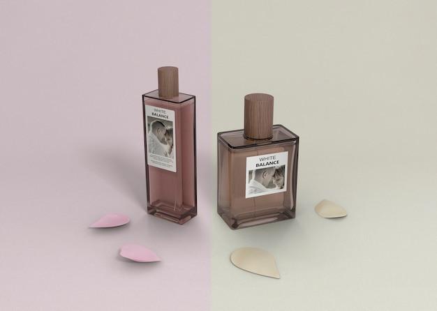 Butelki perfum na stole z płatkami obok