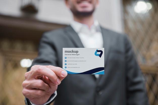 Buźka biznesmen trzyma wizytówkę