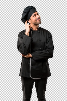 Chef man w czarnym mundurze stoi i myśli pomysł podczas drapania głowy