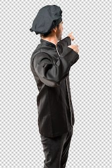 Chef man w czarnym mundurze wskazując z palcem wskazującym przedstawiający produkt od tyłu