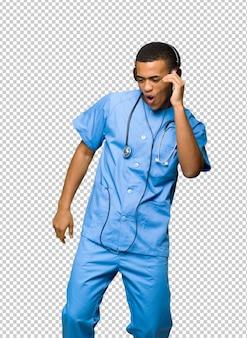 Chirurga lekarki mężczyzna słucha muzyka z hełmofonami i tanem