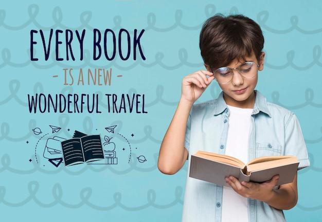 Chłopiec czyta z makiety książki