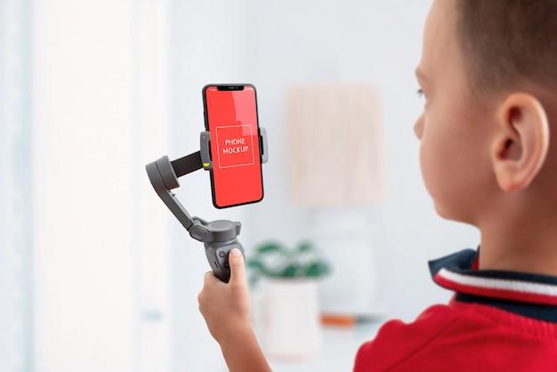 Chłopiec trzyma gimbala z makietą smartfona w pozycji pionowej. zsolone tło. koncepcja fotografowania i fotografii telefonem komórkowym. oddzielone tło