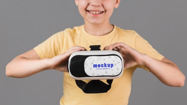 Chłopiec trzyma słuchawki wirtualnej rzeczywistości