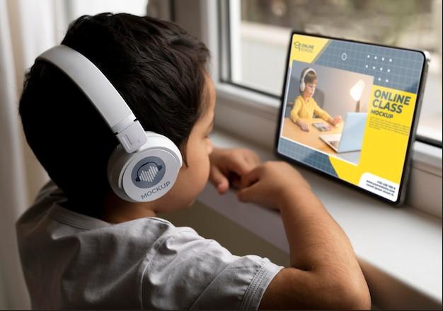 Chłopiec ze słuchawkami za pomocą tabletu