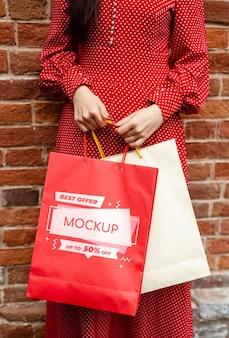 Close-up kobieta trzyma torby na zakupy na zewnątrz
