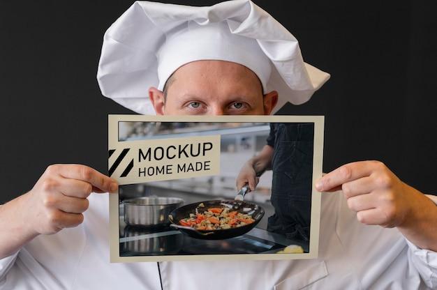 Close-up kucharz trzyma ulotkę