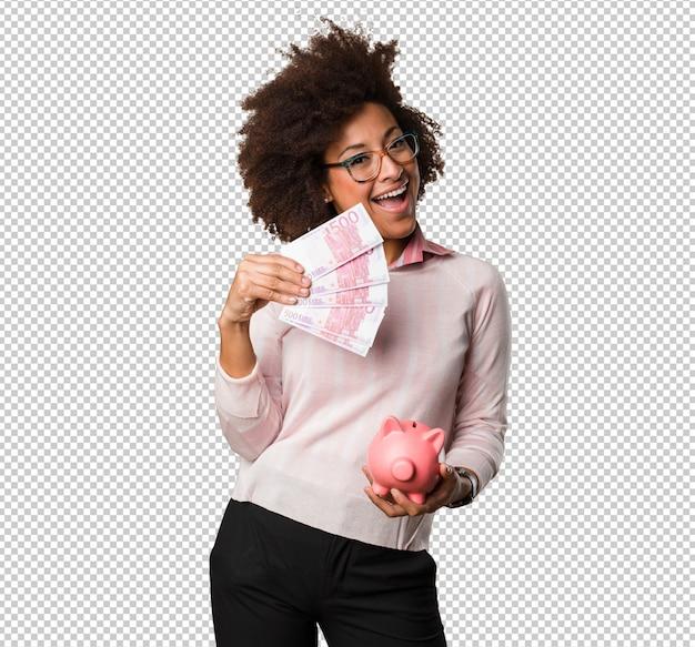 Czarna kobieta trzyma skarbonkę i rachunki