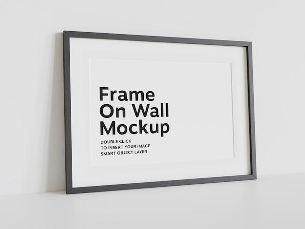 Czarna ramka oparta na ścianie makieta