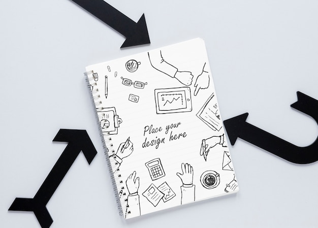 Czarne strzałki i notebook z gryzmoły