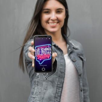 Czarny piątek makieta z kobieta trzymając smartfon