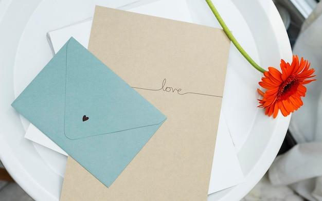 Czerwona stokrotka z beżową literą i niebieską makieta koperty