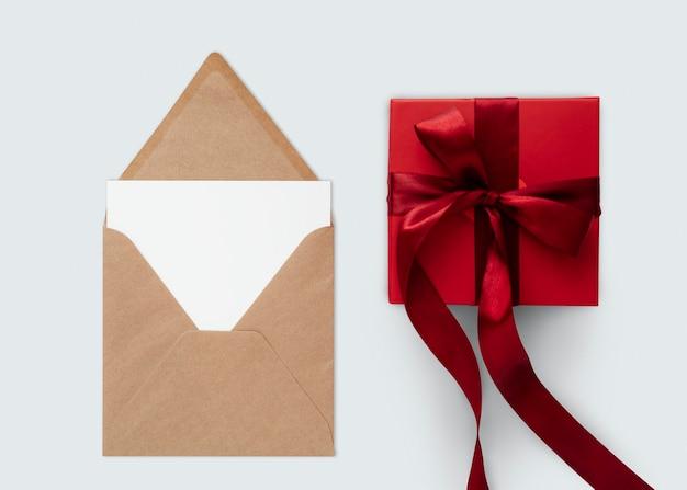 Czerwony prezent przy brązowej makiecie koperty