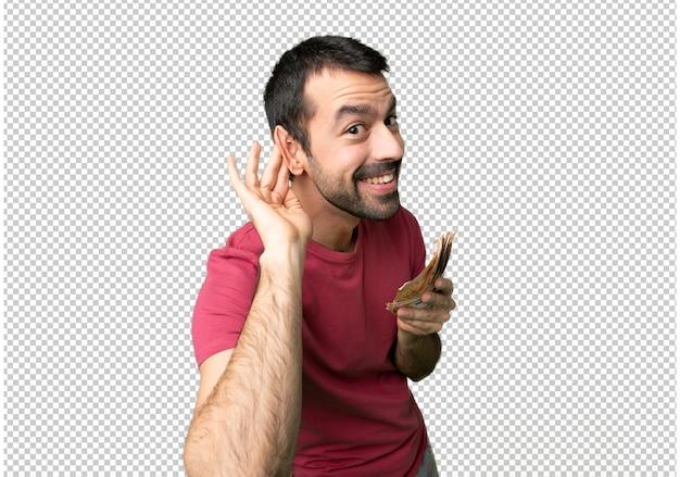 Człowiek biorąc dużo pieniędzy słuchając czegoś, kładąc rękę na ucho