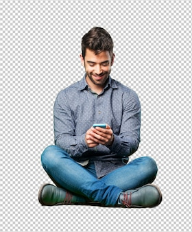 Człowiek siedzący na podłodze zdumiony telefonem komórkowym