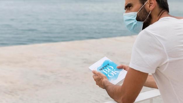 Człowiek z maską na ulicy czytania książki