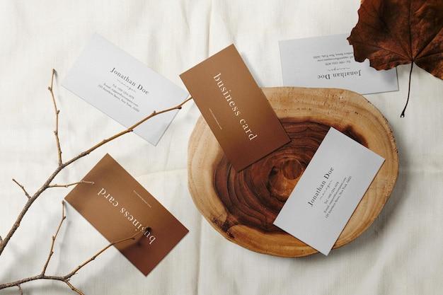 Czysta minimalna makieta wizytówki na drewnianym talerzu i białej tkaninie
