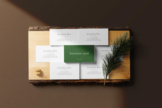 Czysta minimalna makieta wizytówki na drewnianym talerzu z liśćmi