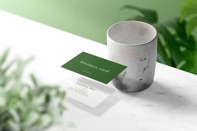 Czysta minimalna makieta wizytówki unosząca się na marmurze z liśćmi i wazonem