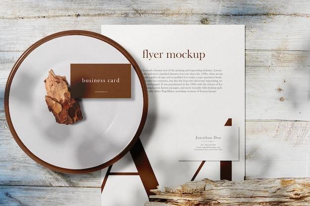 Czysta minimalna wizytówka i papierowa makieta a4 na drewnianym blacie z talerzem
