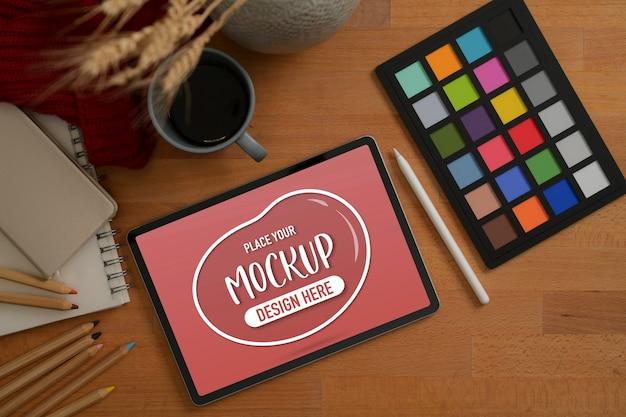 Designerska przestrzeń robocza z makietą tabletu, kontrolerem kolorów i kawą