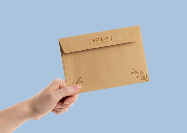 Dłoń trzymająca makietę koperty