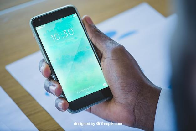 Dłoń trzymająca smartphone w biurze
