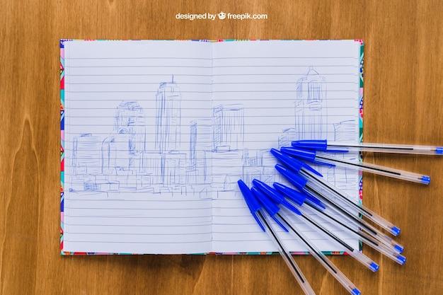 Długopisy i notes na drewnianym stole