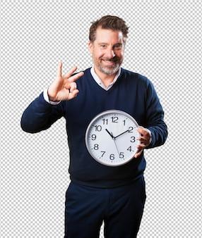 Dojrzały mężczyzna trzyma zegar