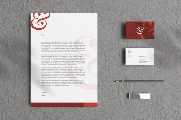 Dokument firmowy a4 z wizytówką i makietą materiałów biurowych w szarym otoczeniu