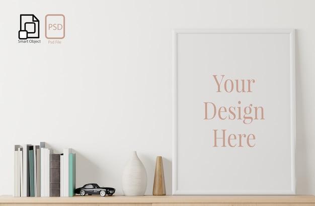 Domowy plakat wewnętrzny makieta z ramą, książką i zabawką na tle podłogi i białej ściany.
