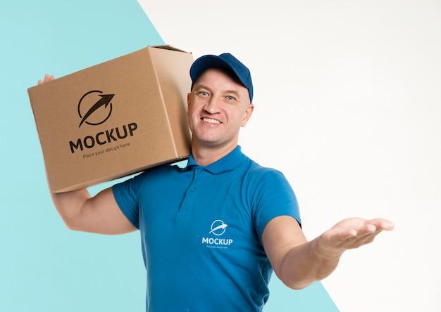 Dostawa mężczyzna trzyma pudełko na ramieniu