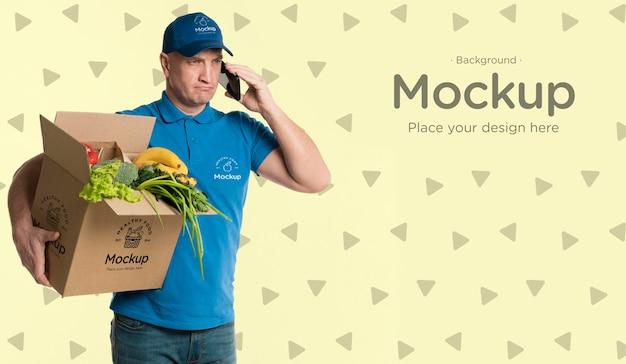 Dostawa mężczyzna trzyma pudełko z makietą warzyw