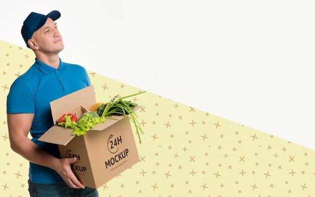 Dostawa mężczyzna trzyma pudełko z makietami różnych warzyw