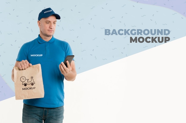 Dostawa mężczyzna trzyma torbę na zakupy, patrząc na swój telefon
