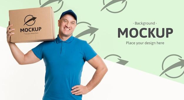 Dostawczy mężczyzna trzyma pudełko na ramieniu z makietą tła
