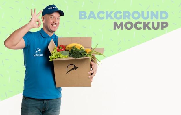 Dostawczy mężczyzna trzyma pudełko pełne makiet warzyw
