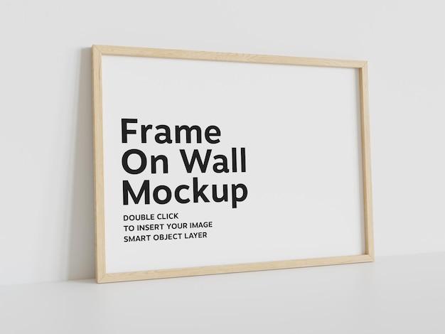 Drewniana rama oparta na białej ścianie makieta