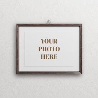 Drewniana ramka na zdjęcia makieta na białym tle na ścianie