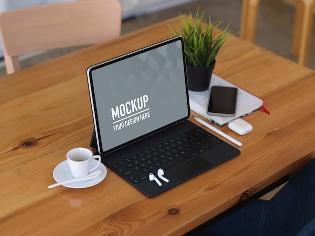 Drewniany stół z makietą cyfrowego tabletu, filiżanką kawy, smartfonem i akcesoriami
