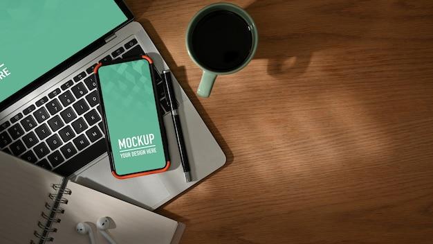 Drewniany stół z makietą smartfona i laptopa, filiżanka kawy, artykuły papiernicze