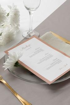 Duży kąt makiety menu wiosennego na talerzu ze sztućcami i kwiatami